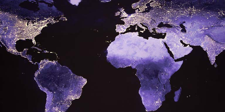 A black and purple map of the world with points of light representing more populated areas.