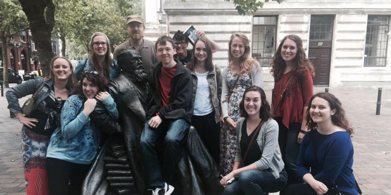 Students pose with statue in London