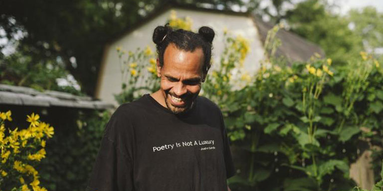 Ross Gay in a garden smiling