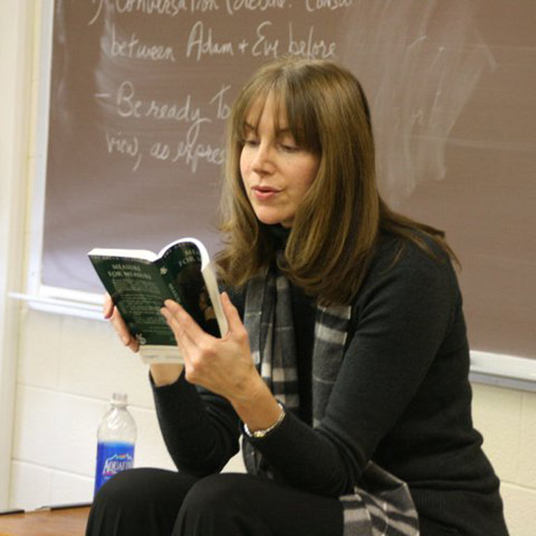 woman sitting in a classroom reading a book a loud.